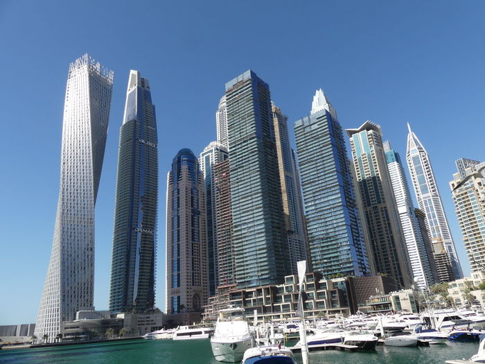 Skyscrapers at the Marina, Dubai, United Arab Emirates 2019 Dubai UAE 2019 Marina Blue Sky Sunlight And Shade Low Angle View No People Cityscape Modern Architecture Modern Design Tower Blocks Towers Skyscrapers Tall - High Urban Skyline Water Boats Composition Outdoor Photography Glass And Steel Buildings Glass And Steel Structure Tourist Attraction  Apartments Famous Place