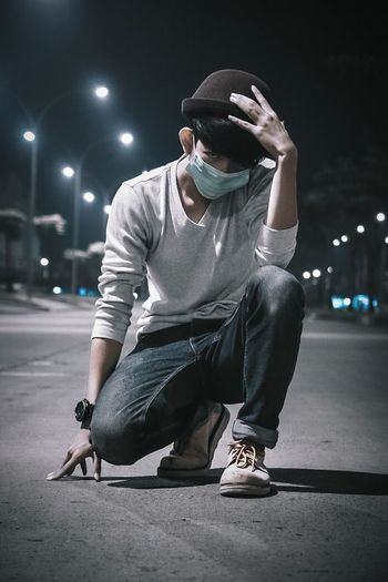 YOUNG MAN WITH SURGICAL MASK OUTDOORS
