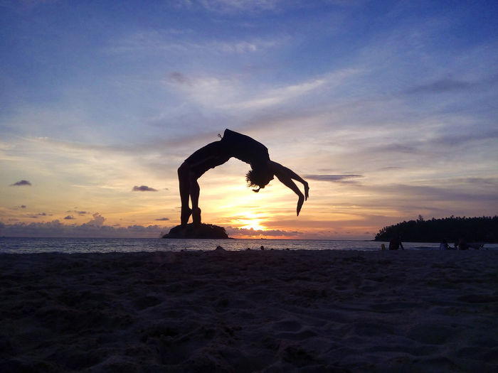 Gymnastics Freerunning Backflip Arms Raised Beach Beauty In Nature Cloud - Sky Handstand  Horizon Horizon Over Water Human Arm Land Lifestyles Mid-air Nature Outdoors Real People Scenics - Nature Sea Silhouette Sky Sport Sunset Tranquil Scene Tranquility Water