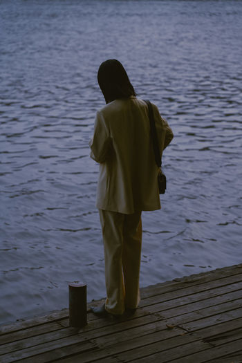 Rear view of woman standing on pier over lake