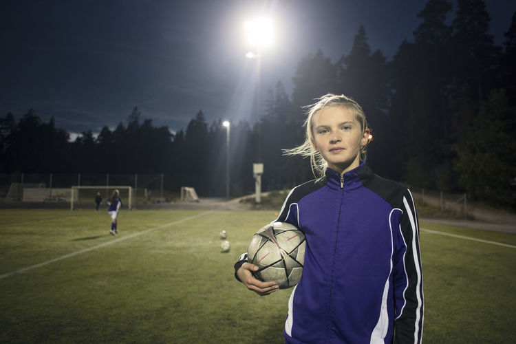 Portrait of boy playing soccer ball on grass at night