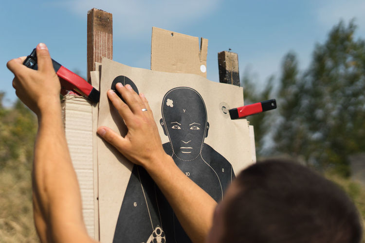 Cropped image of man adjusting clamp on shooting target