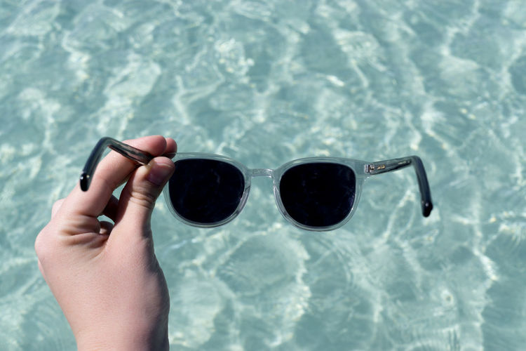 Cropped hand of woman holding sunglasses over swimming pool
