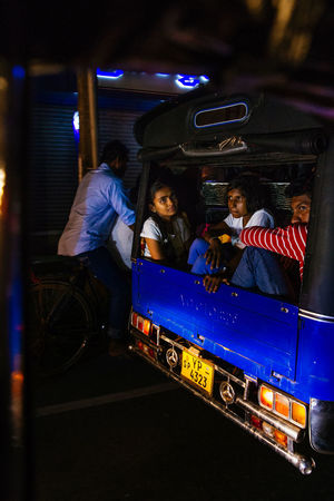 The streets were bustling and writhing with energy in Galle as Sri Lankans celebrated Vesak, the day of Buddah. Shooting from a Tuk Tuk in low light is extremely difficult in ever changing circumstances with light shifting every time traffic moves. The Street Photographer - 2018 EyeEm Awards The Traveler - 2018 EyeEm Awards Females Group Of People Illuminated Land Vehicle Leisure Activity Lifestyles Mode Of Transportation Night Public Transportation Real People Rickshaw Transportation Travel Tuk Tuk Women