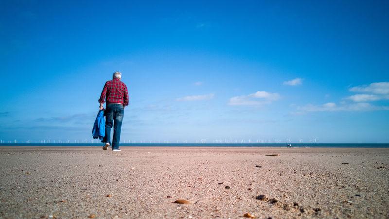 walk along the beach Honor 10 Blue Sky And Clouds United Kingdom Blue Sky Beach Shore Man Walking Stroll Sea Full Length Beach Headwear Blue Sand Dune Sand Men Bicycle Summer Shore