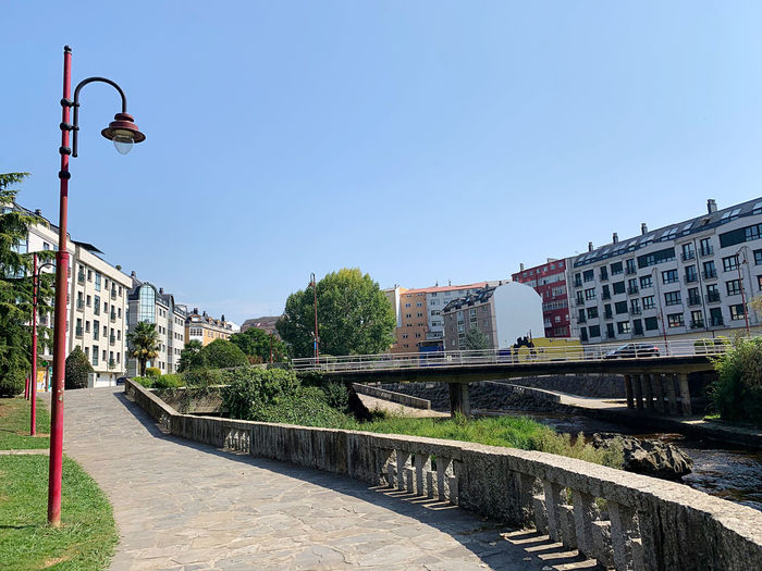Bridge over canal by buildings against clear blue sky