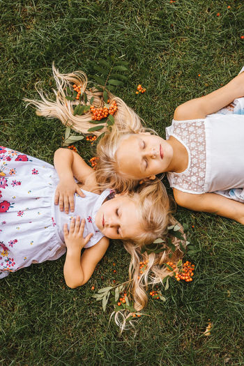 High angle view of sisters lying on grassy land in park