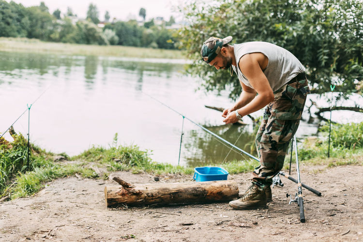 A young fisherman catches fish on a lake or river, prepares tackle and bait. hobbies, weekends