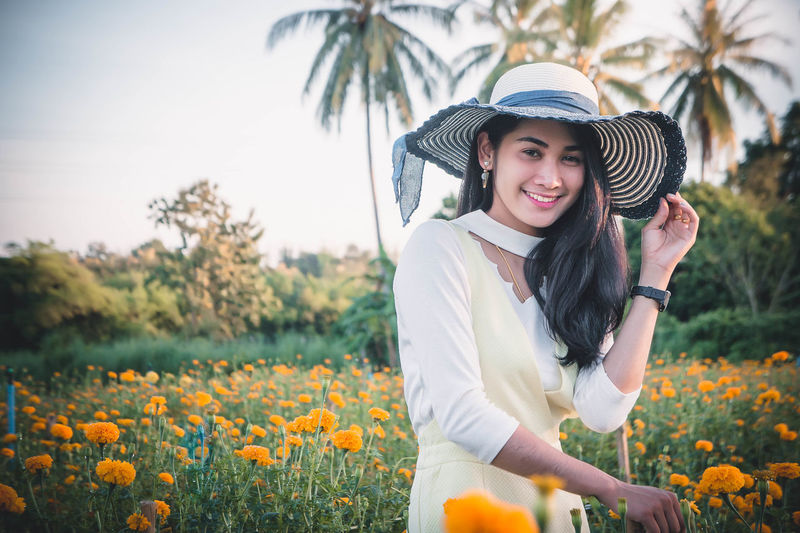 Young woman wearing hat while standing amidst flowers on field