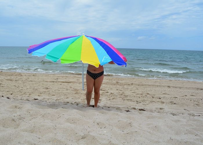 Woman under colorful parasol standing at sandy beach