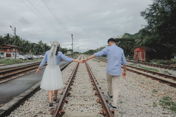 People walking on railroad tracks against sky