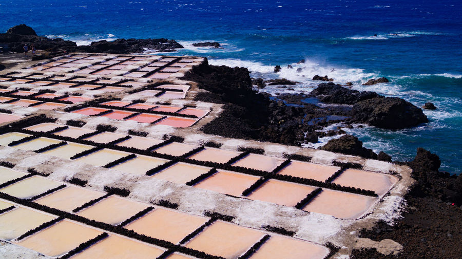 Salt flats farms showing red pink water and white rock sea salt in la palma canary island