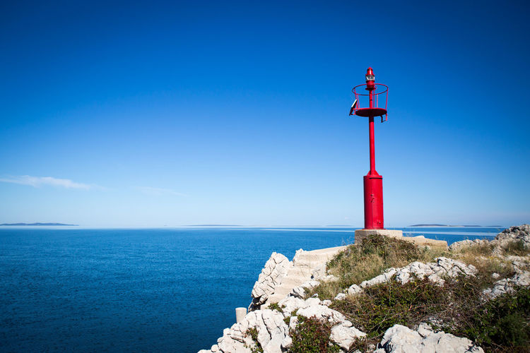 lighthouse Architecture Beach Beauty In Nature Blue Building Exterior Clear Sky Day Direction Guidance Horizon Over Water Lighthouse Nature No People Outdoors Red Safety Scenics Sea Sky Tranquil Scene Tranquility Water