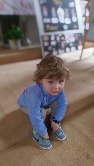 Portrait of cute boy touching shoes