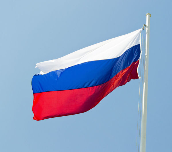 Low angle view of russian flag against clear blue sky
