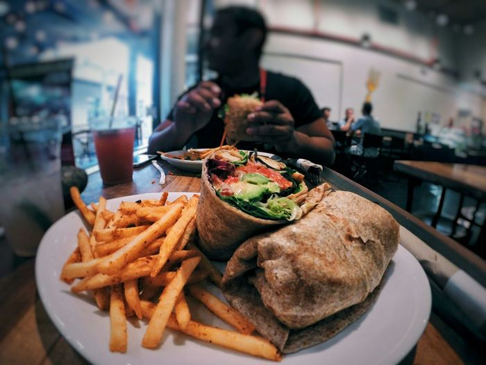 Wrap Sandwich And French Fries Served In Plate At Restaurant