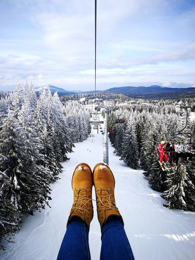 Low Section Of Person Wearing Shoes Over Forest Against Cloudy Sky During Winter