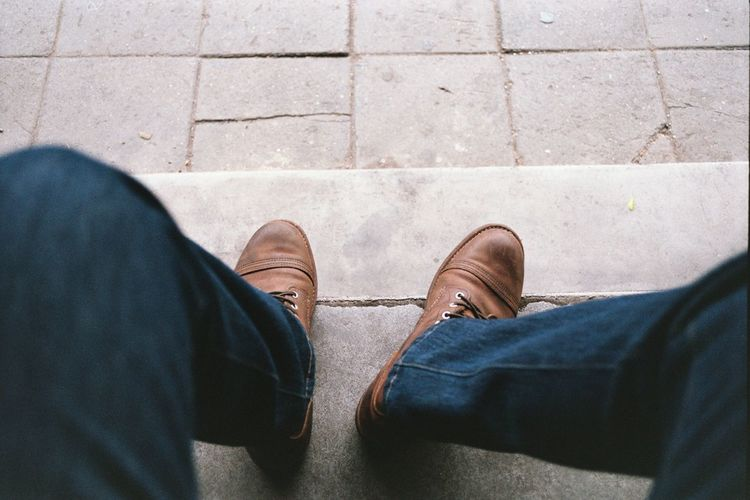 Low section of man sitting on footpath