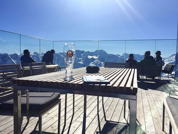 Clear Sky Real People Sitting Sunlight Outdoors Sunny Winter Day Alps Skiing Brake Veranda Restaurant Sitting Outside Restaurant Table Lounge Lounge With A View Empty Glass Bear Table Outside Mountains Mountain Range Mountain View