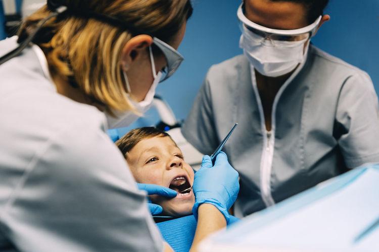Dentist examining boy in medical clinic