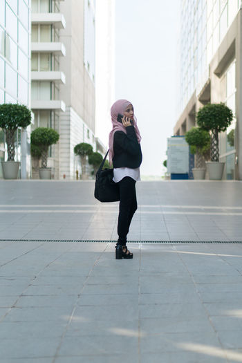 Full length of businesswoman wearing hijab and suit standing in city