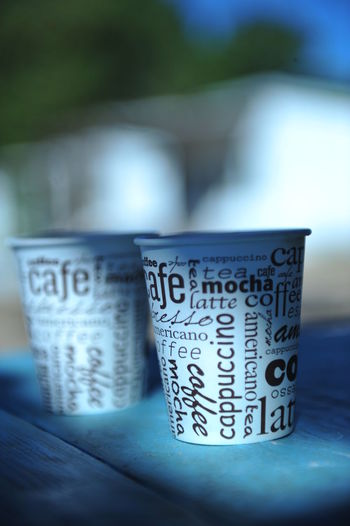 Close-up of text on disposable cups at table