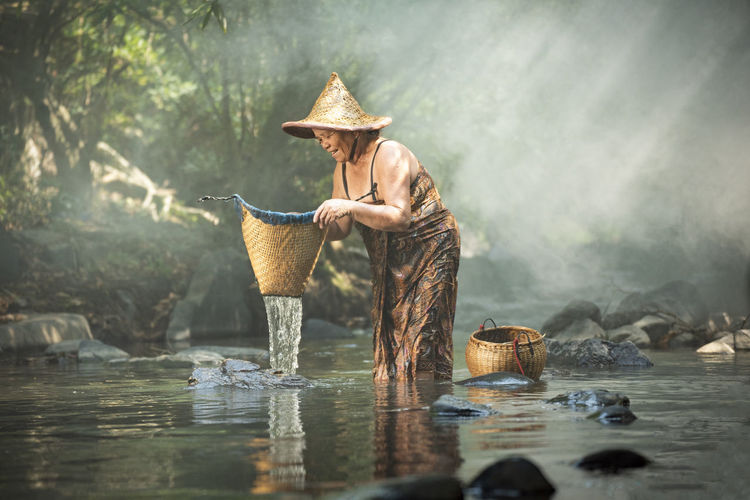 Woman holding whicker basket in river
