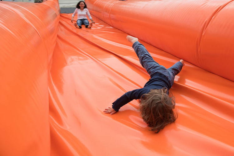 Low Angle View Of Mother With Daughter Sliding On Bouncy Castle
