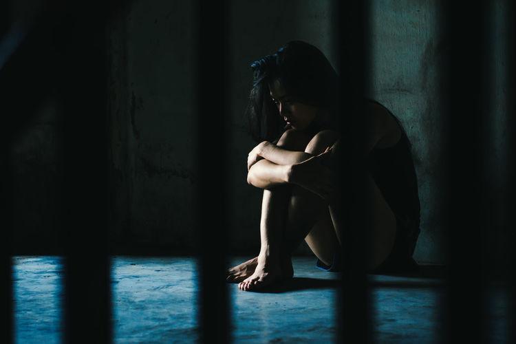 Side view of depressed woman sitting on floor