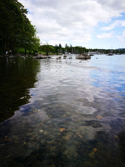 Surface of the water Lake Windermere Lake Transparent Water Rocky Beach Reflection On The Water Blue Yacht Stalling Boats Boats Clouds May Stones Trees Vertical People Huawei p9 Cumbria Uk Holiday