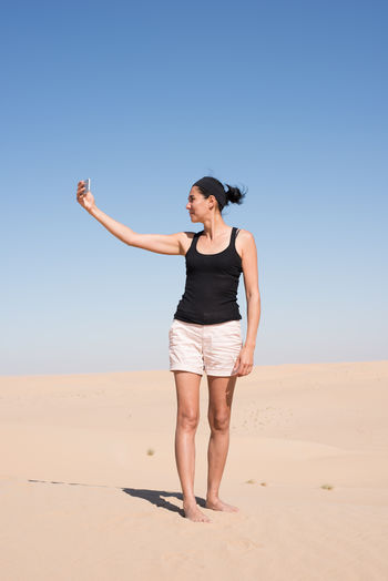 Woman in the 40s taking a selfie in the desert of Dubai, UAE Desert Arid Climate Clear Sky Climate Day Desert Front View Full Length Horizon Human Arm Land Leisure Activity Nature One Person Outdoors Real People Sand Scenics - Nature Self Portrait Selfie Sky Standing Sunlight Women Young Adult