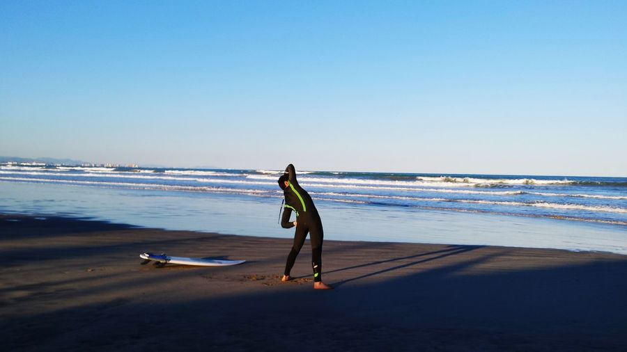 Full length of surfer standing at beach against clear blue sky