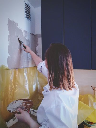 Rear view of woman painting wall