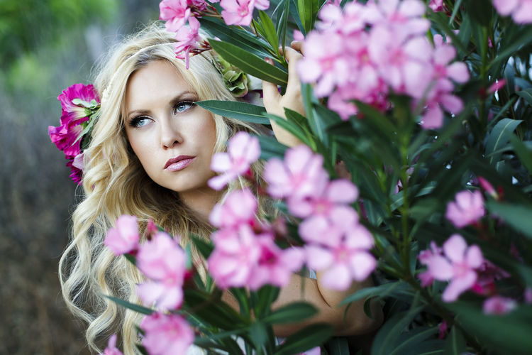 Bucolic portrait of young beautiful blond Caucasian female with blue eyes and wavy long hair surrounded by pink flowers and green leaves in forest Beautiful Woman Beauty Beauty In Nature Blond Hair Flower Flower Head Flowering Plant Fragility Freshness Hair Hairstyle Looking At Camera One Person Outdoors Pink Color Plant Portrait Real People Vulnerability  Women Young Adult Young Women