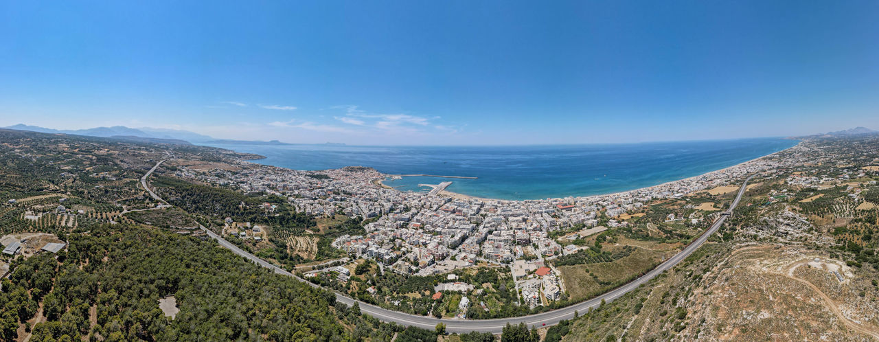 Panoramic view of sea and cityscape against blue sky