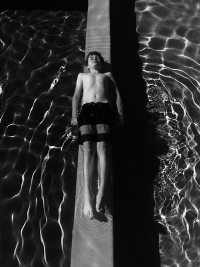 High angle view of boy resting on retaining wall in swimming pool