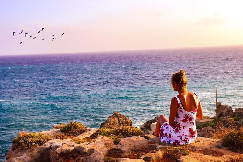Golden Bay in Malta Sunset Sea Water Sky Beauty In Nature Nature Beach Lifestyles Leisure Activity Scenics - Nature Land Horizon Over Water Real People Horizon Sitting One Person Women Rock Outdoors Summer Road Tripping The Traveler - 2018 EyeEm Awards My Best Photo