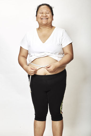 Smiling overweight woman measuring stomach while standing against white background