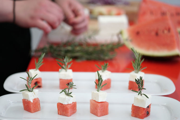 Close-up of watermelon and feta cheese cubes with rosemary on cutting board