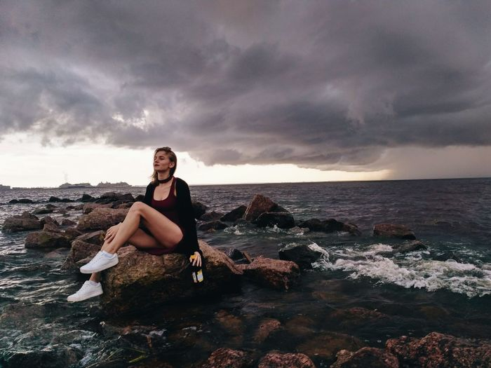 Beautiful fashion model sitting with liquor bottle on rock in sea against cloudy sky