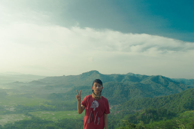 Portrait of man showing peace sign while standing on mountain against cloudy sky