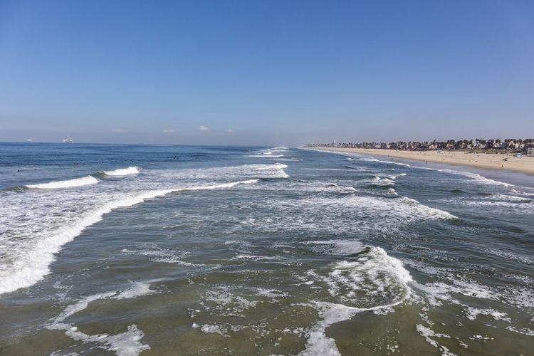 Huntington Beach coastline Sea Water Wave Motion Beach Land Clear Sky Scenics - Nature Beauty In Nature Sky Aquatic Sport Sport Surfing Nature Copy Space Day Horizon Horizon Over Water Outdoors Power In Nature Huntington Beach Orange County
