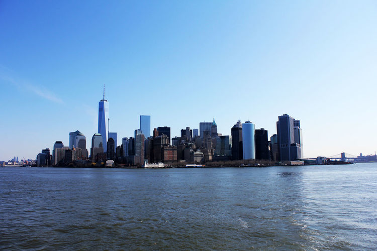 Manhattan city at waterfront against blue sky