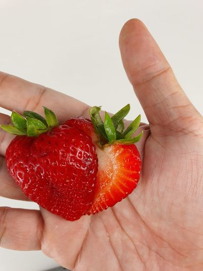 Cropped image of hand holding strawberries