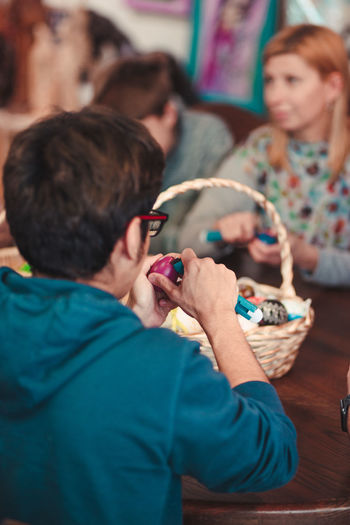 Rear view of young man decorating easter eggs while sitting on table indoors