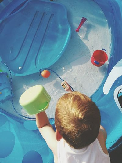 Rear View Of Playful Boy With Toys In Wading Pool