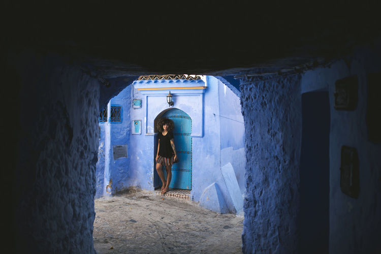 Adult Africa Arch Architecture Blue Building Built Structure Day Door Entrance Full Length Indoors  Lifestyles Men Morroco One Person Real People Rear View Standing Tunnel Wall - Building Feature Women