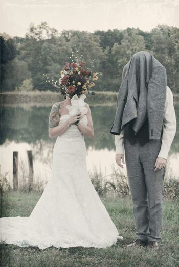 Bride Covering Face With Bouquet And Groom With Coat While Standing On Field