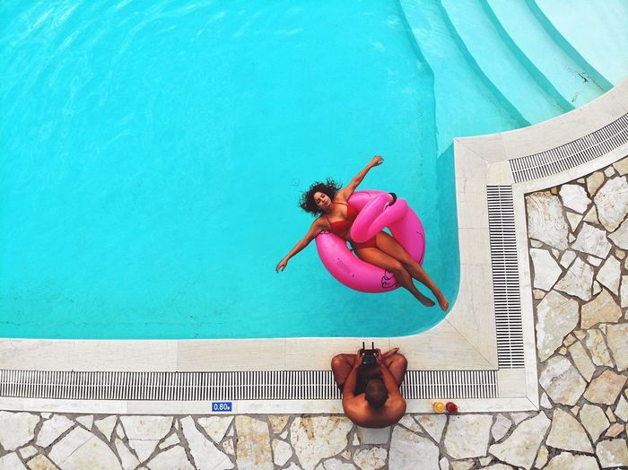 High angle view of woman swimming in pool while man sitting on poolside