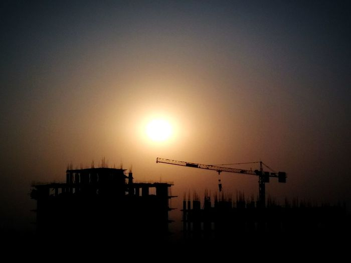 A sunset view from my work place 👆😍😇 Engineerlife Engineering Design City Sunset Cityscape Silhouette Clear Sky Sun Urban Skyline Sunlight Sky Architecture Crane - Construction Machinery Architectural Style Construction Site Commercial Dock Crane Construction Vehicle